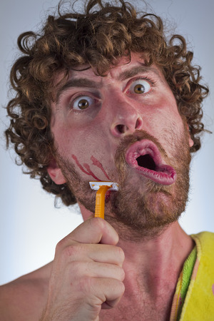 appalled: Silly bearded man cuts his face while shaving off his beard Stock Photo