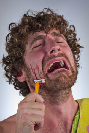 Silly bearded man cuts his face while shaving off his beard Stock Photo