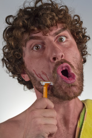 haste: Shocked curly haired man shaves off his beard