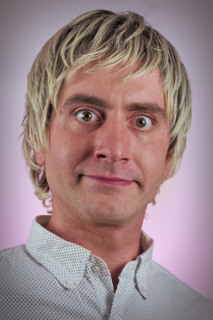 hurtful: Grinning silly man with blonde hair and wide eyes Stock Photo