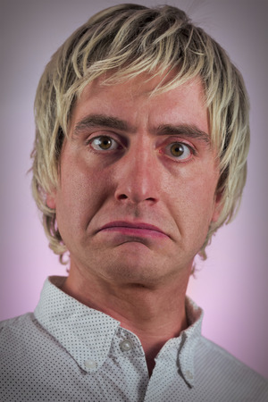frowns: Sad blonde haired man frowns in studio portrait