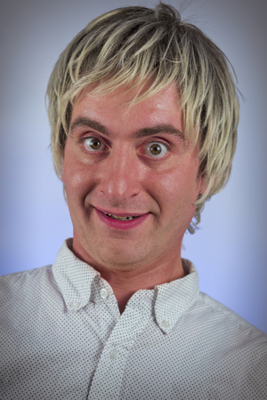 sarcastic: Grinning silly man with blonde hair and wide eyes Stock Photo