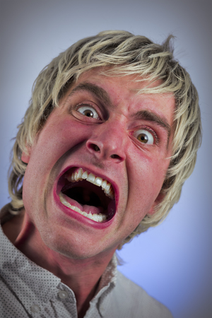 provoke: Angry blonde man screams at the top of his lungs