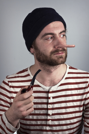 stubbly: Lying bearded sailor grimacing while smoking a pipe