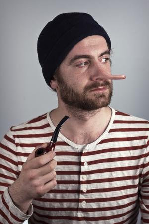 panache: Lying bearded sailor grimacing while smoking a pipe