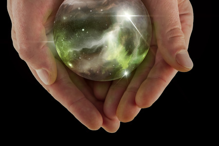Holding the universe in fortune teller magic crystal ball Stock Photo