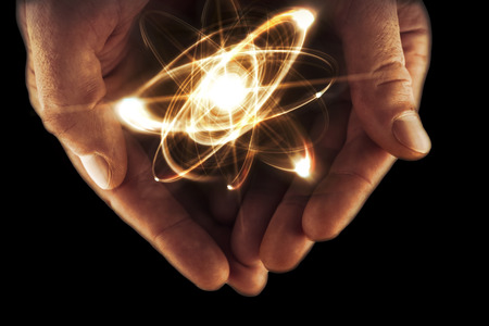 orbiting: Atomic orbitting particle being held in cupped hands