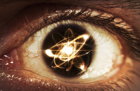 neutrons: Atomic particle reflection in the pupil of an eye for physics background Stock Photo