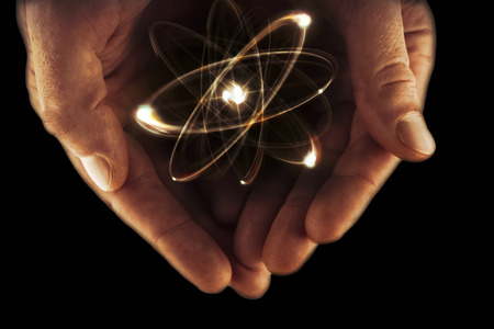 splitting: Atomic orbitting particle being held in cupped hands