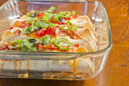 casserole dish: Delicious home made Mexican enchiladas in a casserole dish Stock Photo