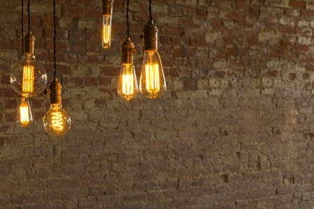 hanging on: Decorative antique edison style light bulbs against brick wall background