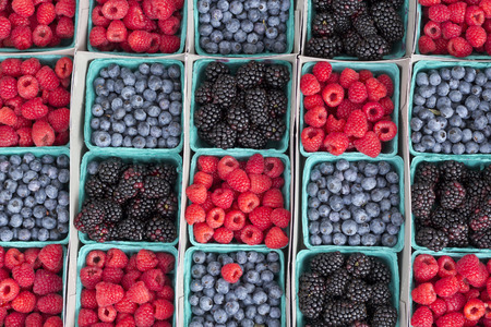 Rows of strawberries blueberries and blackberries at local farmers market