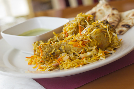 cuisine: Indian cuisine chicken biryani with basmati rice and green sauce