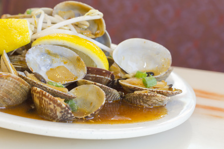 Chinese baby clams sauteed in sweet and spicy black bean sauce with lemon wedge Banco de Imagens