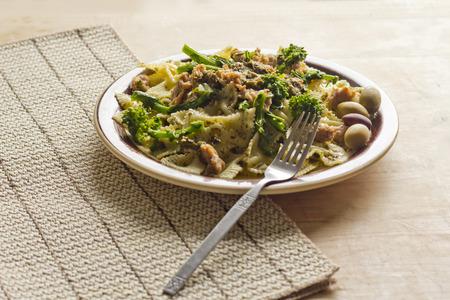 plato de comida: Pajarita pasta al pesto con salchicha suelo y br�coli rabe adornado con aceitunas de lujo Foto de archivo