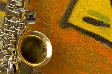 saxofón: Lone saxofón de edad se inclina contra la pared de ladrillo fuera abandonada club de jazz