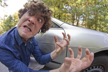personas enojadas: Hombre tonto mete en accidente de coche y hace cara ridícula Foto de archivo