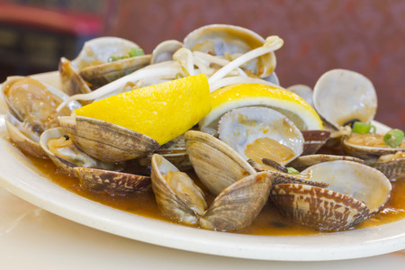 lemon wedge: Chinese baby clams sauteed in sweet and spicy black bean sauce with lemon wedge Stock Photo