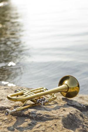 instruments: Summer Jazz trumpet in nature lying on rocks lakeside Stock Photo