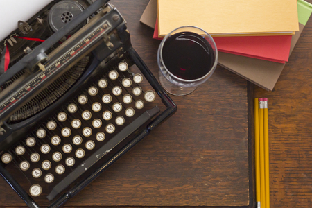 Old vintage typewriter with glass of wine pencils and books in this retro creative writing and relazation themed desk top Stock Photo - 47499259