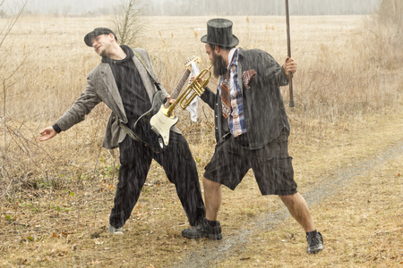 hobo: Stylish gypsies play trumpet and electric guitar on a wilderness path