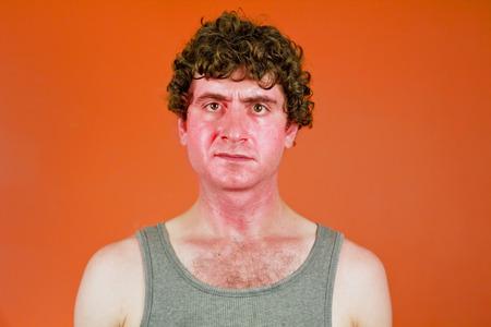 Sunburned sweaty man looks very unhappy in portrait Standard-Bild