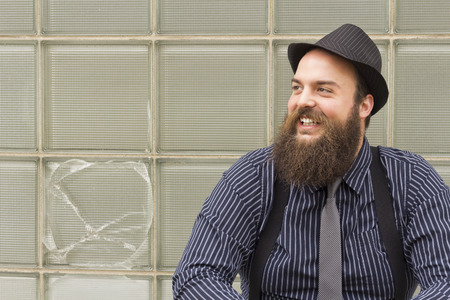 snazzy: Stylish bearded man laughs with delight by broken window Stock Photo