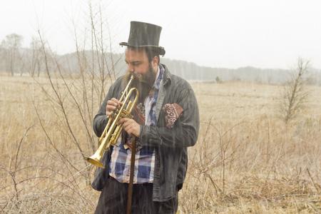 hobo: Stylish bearded gypsy plays trumpet on a wilderness path Stock Photo