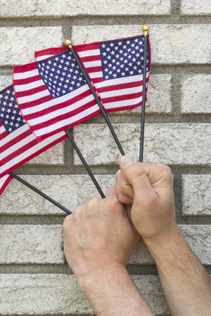 clench: Fists clench small American flags in patriotic imagery