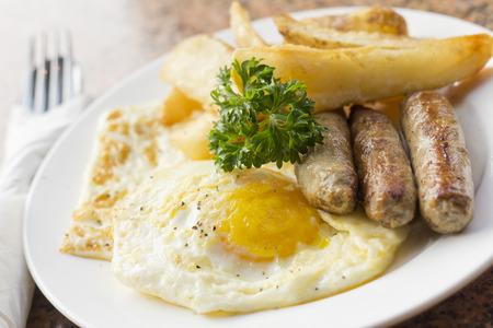 papas doradas: Huevos fritos con patatas fritas caseras desayuno de salchichas y perejil
