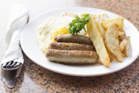 desayuno: Huevos fritos con patatas fritas caseras desayuno de salchichas y perejil