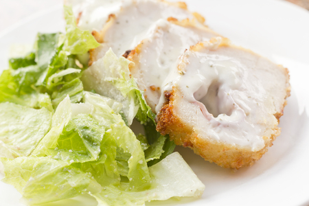 cordon: Sliced chicken cordon bleu with creamy sauce and romane leaf salad Stock Photo