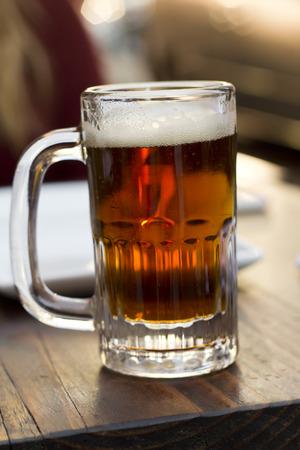 foamy: Foamy mug of cold beer dark color with lots of hops