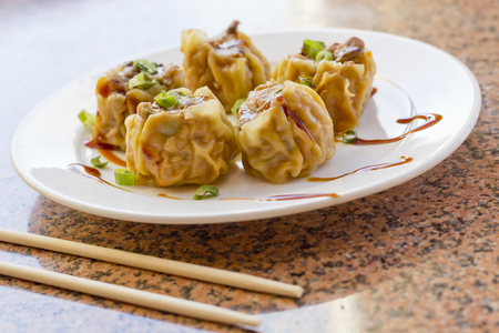 scallions: Delicious Chinese Dim Sum dumplings topped with scallions and sweet sauce