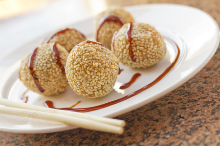 food       plate: Fancy Chinese dessert sesame donuts with sweet brown sauce