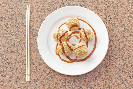 plato de comida: Fancy rosquillas postre s�samo chinos con salsa de caramelo de color marr�n