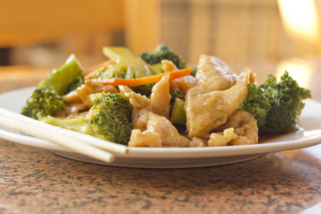 Chinese food chicken with broccoli take out with chopsticks Stock Photo