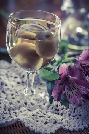 wildflowers: Sweet Japanese plum wine with fruit in glass photographed with beautiful pink wildflowers