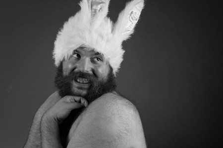 man with hat: Embarrassed bearded fat man wears silly bunny ears
