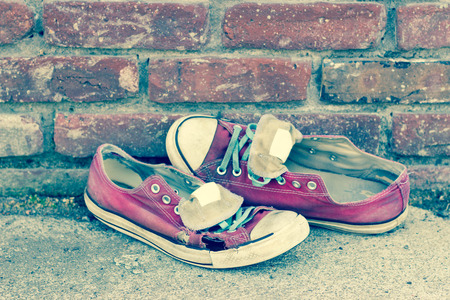 Pair of old smelly worn classic sneakers leaning against a brick wall
