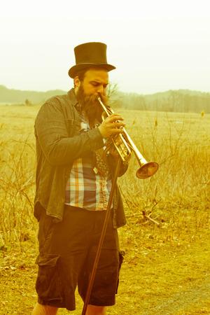 gypsy: Stylish bearded gypsy plays trumpet on a wilderness path Stock Photo