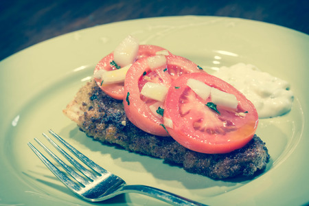 tartar: Breaded cod fillet with tomato and onion with tartar sauce Stock Photo