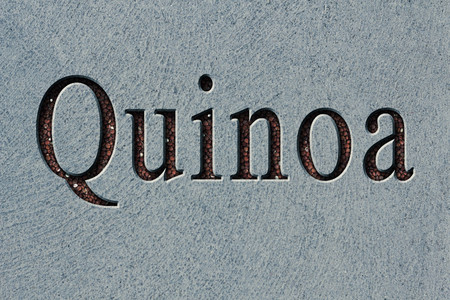 etch: Text engraving word quinoa with quinoa grains filling up the engraving Stock Photo