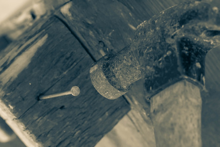 Old and worn contracting hammer and three nails on a distressed work bench