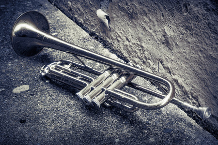 pealing: Old worn trumpet stands alone in alleyway behind a jazz club