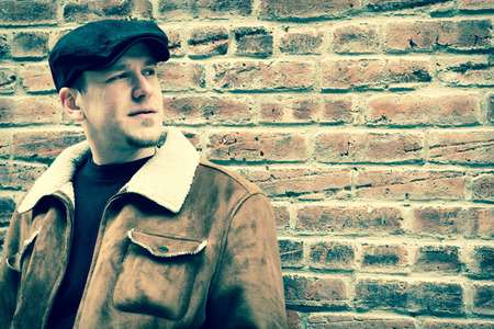 newsboy cap: Cool guy rocks an aviator jacket and newsboy cap as he takes a moment to think