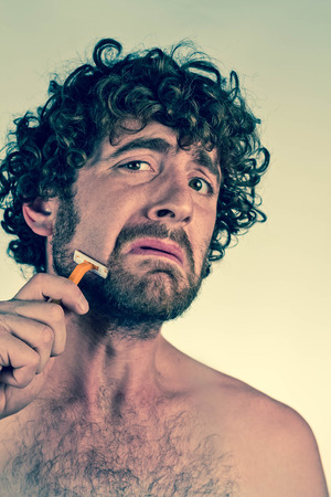 cutting hair: Silly curly haired man shaves off his beard Stock Photo