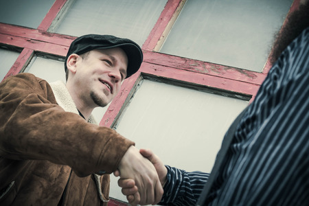 snazzy: Two well dressed friends shake hands as they greet eachother on a city street