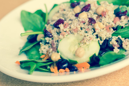 red gram: Fresh and healthy quinoa salad on bed of spinach with dried cranberries Stock Photo