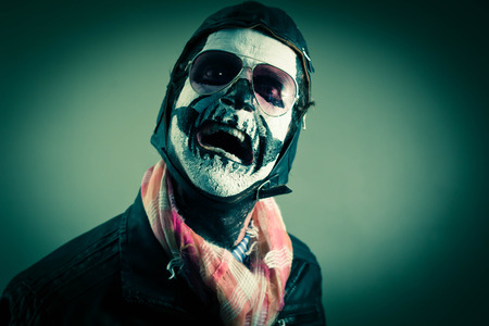 Scared aviator with face painted as human skull Stock Photo